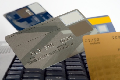 A selection of credit cards and a computer keyboard being used for online purchases.
