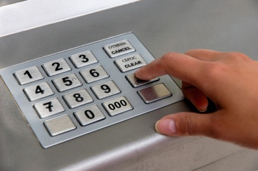 A person using PIN-pad at a bank machine.
